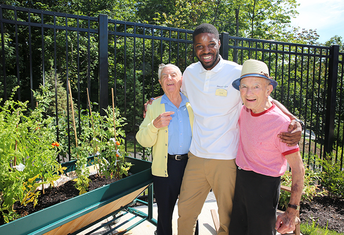 Wellspring Village Memory Care Residents enjoying outdoor patio and laughing with Brightview associate