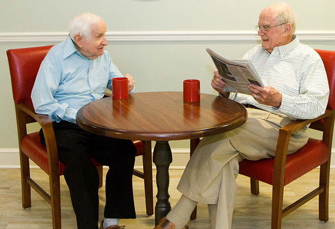 Brightview Wellspring Village Memory Care Residents reading newspaper and having coffee together
